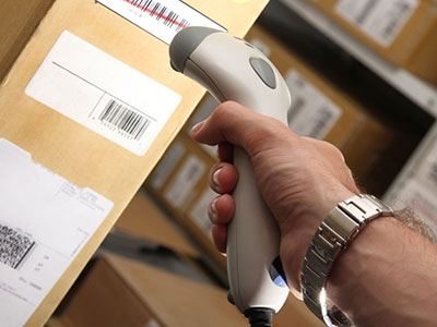 Image of cropped hand holding a tan barcode scanner scanning a barcode on a brown shipping box